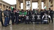 """Machtdemonstration: Mitglieder der """"Guerilla Nation Vaynakh"""" posieren mit tschetschenischen Flaggen in Berlin."""