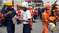 Feuerwehrmann Jorge Flores erklärt einer Nachwuchskraft, worauf es bei einer Katastrophenübung ankommt.
