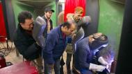 Der Funke springt über: Die Projektteilnehmer Mahmood Golestani, Ahmed Ahmedov, Rahman Area und Egsan Sediqi (von links) schauen Schweißereimeister Manfred Macheit über die Schulter.