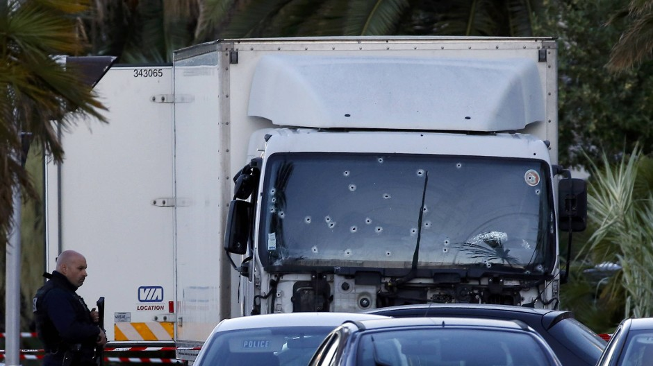 French CRS police secure the heavy truck that ran into a crowd at high speed killing scores celebrating the Bastille Day July 14 national holiday on the Promenade des Anglais killing 80 people in Nice