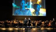 Diana Haller singt als Hänsel mit dem Staatsorchester Stuttgart unter der Leitung von Georg Fritzsch. Auf der Leinwand spielen Ariane Gatesi (l.) und David Niyomugabo Gretel und Hänsel in Ruanda.
