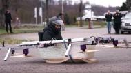 Die Badewannen-Drohne landet auf dem Parkplatz einer Bäckerei. Schaulustige dokumentieren die skurrile Szene mit ihren Smartphones.