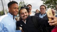 Raheem Sterling posiert mit Anhängern seines neuen Klubs.