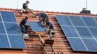 Jetzt noch schnell investieren? Handwerker montieren eine Photovoltaikanlage auf einem Dach in Brandenburg.